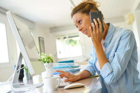 homeoffice: Office worker talking on phone in front of desktop