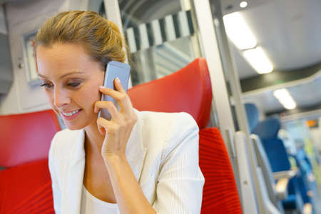 Businesswoman in train working on laptop and talking on phone Stock Photo