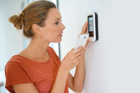Woman using smartphone to control home connectivity interface Foto de archivo