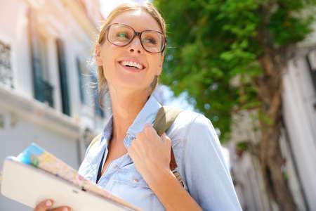 Gelukkig toerist meisje lezen kaart en het gebruik van tablet in de straat Stockfoto