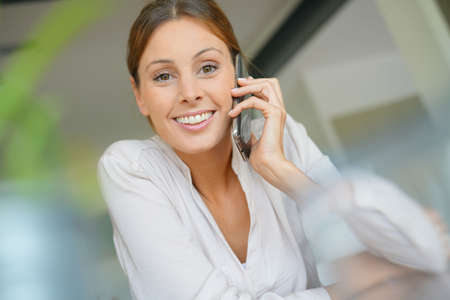 Woman sitting at desk talking on mobile phone Stock Photo