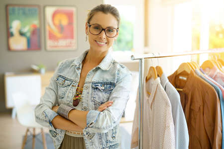 Cheerful clothing salesperson standing in shop Imagens - 80050683