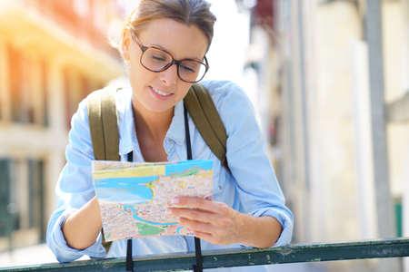 Toerist met rugzak lezen stadskaart Stockfoto