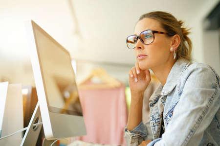 Fashion designer working on computer in workshop