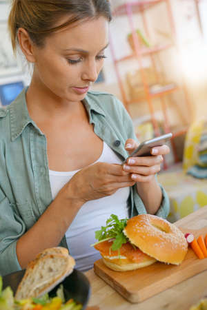Trendy girl in restaurant taking picture of colourful dish with smartphone Stock Photo