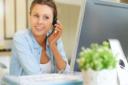homeoffice: Customer service operator talking on phone in office