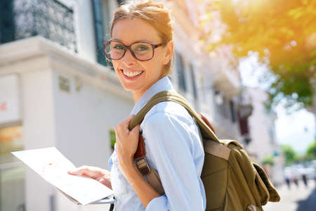 Happy tourist girl reading map and using tablet in the street Stock Photo