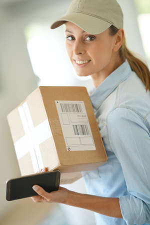 Portrait of smiling delivery woman holding package