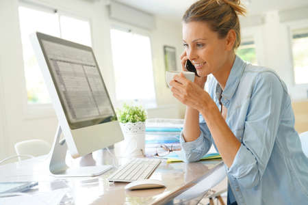 Businesswoman at work talking on phone and drinking coffee Stock Photo