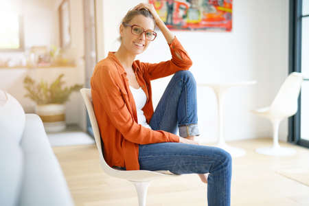 Happy trendy girl sitting on chair in modern house