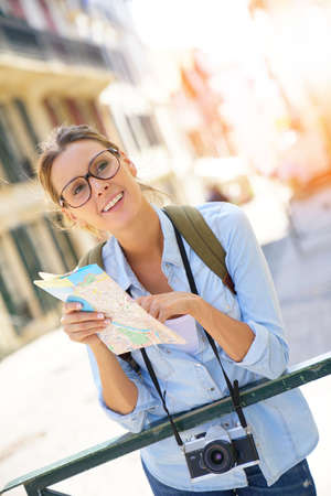 Tourist with backpack reading city map
