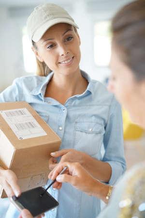 배달 여자가 서명에 대해 고객에게 패키지를 나눠주고 스톡 콘텐츠