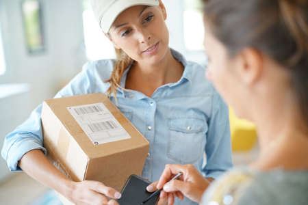 Delivery woman handing package to customer against signature