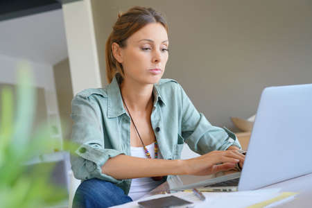 homeoffice: Trendy girl working from home on laptop
