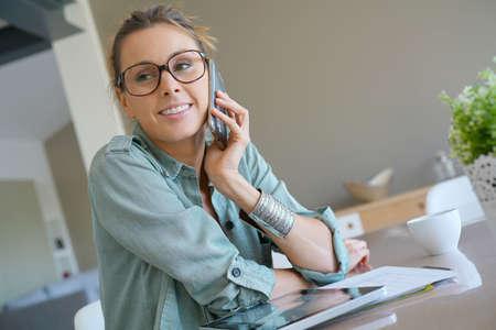 homeoffice: Trendy designer girl talking on phone, home-office