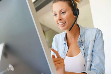 Customer service operator talking on phone in office