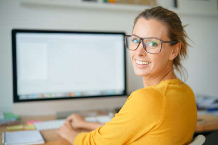 homeoffice: Cheerful trendy girl working on desktop computer Stock Photo