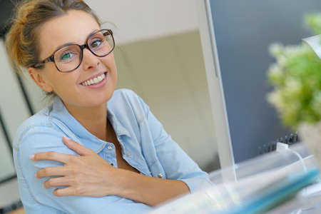 Beautiful young woman in office working on desktop computer