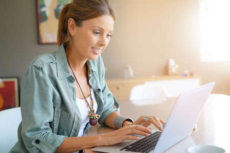 homeoffice: Young trendy woman at home working on laptop