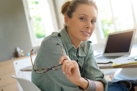homeoffice: Businesswoman with eyeglasses looking at camera