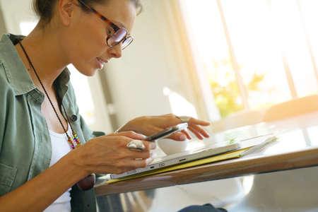 homeoffice: Trendy girl with eyeglasses connected on digital tablet