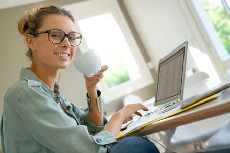 homeoffice: Cheerful woman with eyeglasses drinking coffee in front of laptop Stock Photo