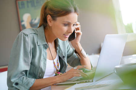 homeoffice: Woman working from home on laptop and talking on phone