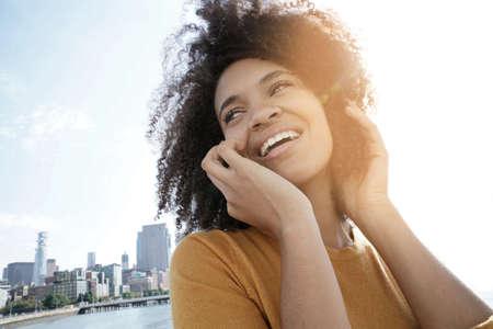 Cheerful mixed raced girl in Manhattan talking on phone