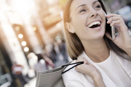 Cheerful girl shopping in Manhattan and talking on phone