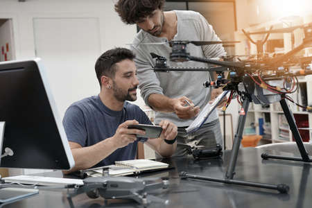 Engineer and technician working together on drone in office Stock Photo