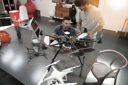 Engineer and technician working together on drone in office Stockfoto