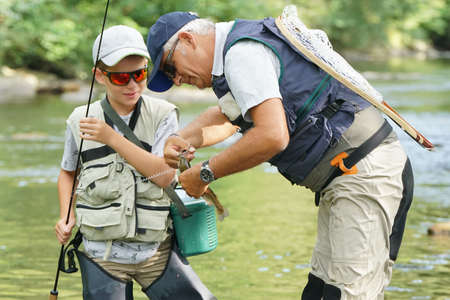 Father and son catching rainbow trout in river