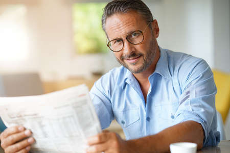 Portrait of mature man with eyeglasses reading newspaper Banque d'images