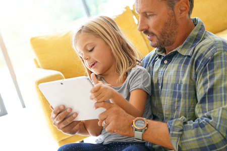 Daddy with little girl connected on digital tablet
