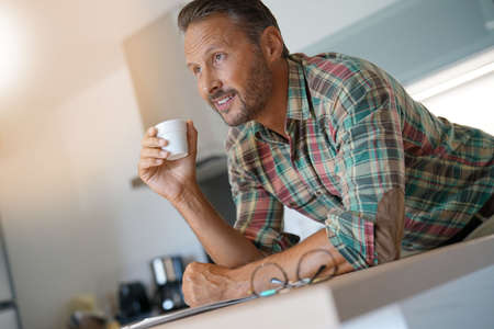 Smiling mature man drinking coffee in home kitchen