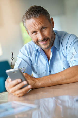 Handsome mature man using smartphone at home Banque d'images