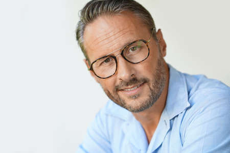 Portrait of mature man with eyeglasses and blue shirt, isolated