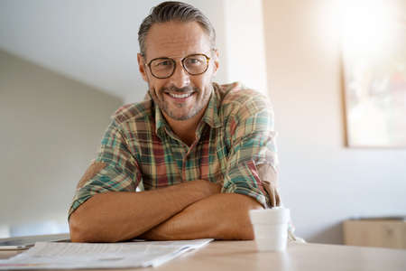 Handsome mature man at home reading newspaper Banque d'images
