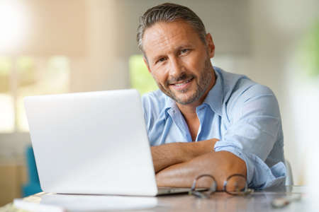 Mature man working on laptop computer at home