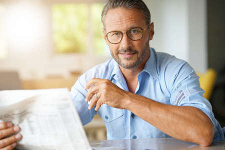 Portrait of mature man with eyeglasses reading newspaper Stock Photo