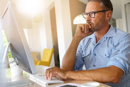 homeoffice: Mature man working from home on desktop computer