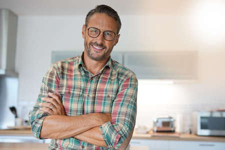 Cheerful mature man with eyeglasses looking at camera