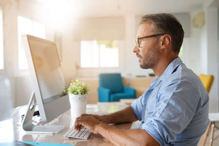 Mature man working from home on desktop computer