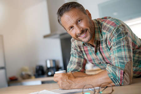 Smiling mature man drinking coffee and reading newspaper