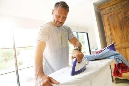Man at home ironing clothes