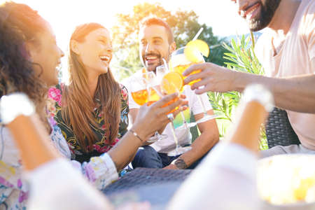 Group of friends cheering with summer cocktails