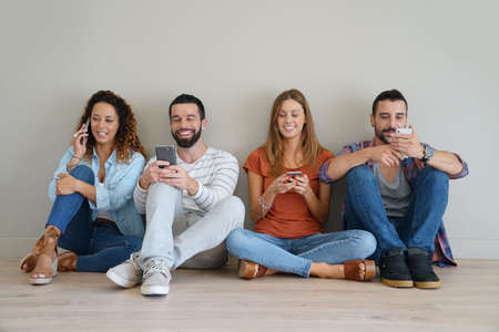 sitted: Group of friends using smartphone, sitted on floor Stock Photo