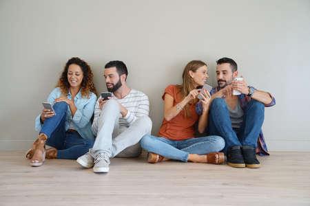 Groupe d'amis utilisant un smartphone, assis sur le sol