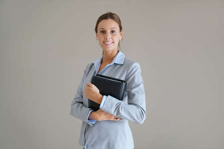Businesswoman standing on grey background, isolated Banque d'images