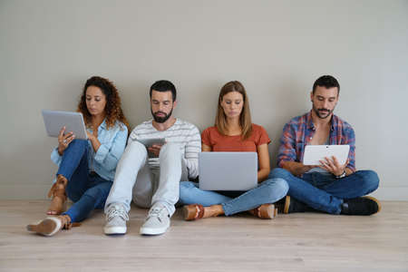 sitted: Group of friends using laptop and tablet, sitted on floor